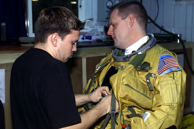 US Air Force Captain Darrell Dunn, U-2 pilot, 363rd Expeditionary Reconnaissance Squadron, Prince Sultan Air Base, Saudi Arabia, gets suited up before his flight with the help of USAF SENIOR AIRMAN John Harry, physiology support. CPT Dunn and SRA Harry are part of the coalition force here to support Operation SOUTHERN WATCH, a military effort to enforce the no-fly and no-drive zone in Southern Iraq