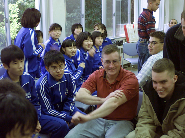 US Marine CPL Thomas G. Bunce, (centered in red), a heavy machine gunner with weapons company, 3rd Battalion, 3rd Marine Division, speaks with students of Tsurushiro Jr. High School. A cultural exchange visit to the school took place near Camp Fuji as part of the unit's community relations effort