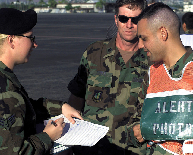 US Air Force Lieutenant Colonel Harvey Jones (Center), Security Alert Response Team (SART) Commander, observes Disaster Control Group (DCG), Alert PHOTO Representative Adrian Cadiz (Right), checking in at the security check point prior to entering the exercise search area on Hickam Air Force Base, Hawaii, on October 30th, 2000. This mission is in direct support of a MAJOR ACCIDENT RESPONSE EXERCISE (MARE)