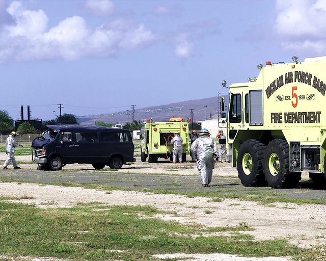 US Air Force Members of the Hickam Air Force Base, Hawaii, Fire Department respond to an accident site. The accident is part of the MAJOR ACCIDENT RESPONSE EXERCISE (MARE), simulating an aircraft accident and aircraft parts striking a POV (Privately Owned Vehicle). The crash rescue squad moves in to try to rescue trapped crash victims in the van, on Hickam AFB, on October 30th, 2000