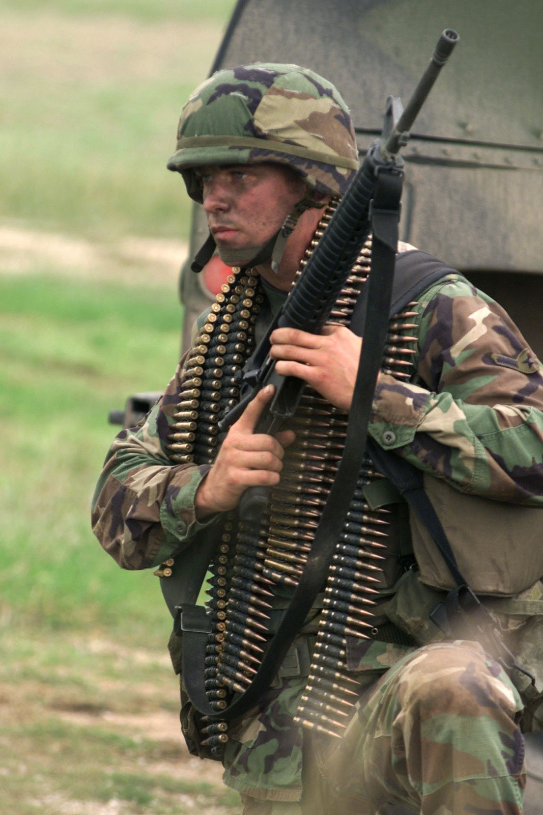 US Air Force AIRMAN Scott J. Paneton, from the US Air Forces in Europe command, waits with an M16A2 rifle and a large amount of ammo to go to his position and compete in the combat weapons competition at Camp Bullis, Texas, during DEFENDER CHALLENGE 2000. Defender Challenge is the annual Air Force wide competition sponsored by Air Force Security Forces. This competition showcases the talents and capabilities of 13 international Security Forces teams in seven physical fitness, base defense and policing skills over six days