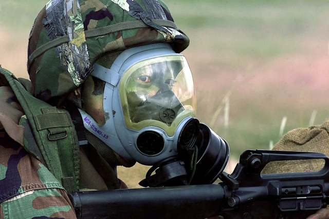 US Air Force Captain Steve Sugiyama, team leader and rifleman from the 11th Wing, dons gas mask during a simulated chemical attack in the Combat Weapons phase of DEFENDER CHALLENGE 2000 at Lackland Air Force Base, Texas. Defender Challenge is the annual Air Force wide competition sponsored by Air Force Security Forces. This competition showcases the talents and capabilities of 13 international Security Forces teams in 7 physical fitness, base defense, and policing skills over six days