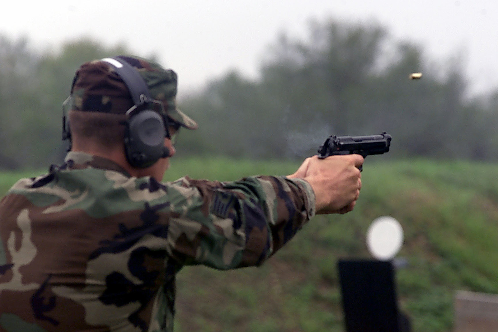 US Air Force STAFF Sergeant Timothy Arnold, a member of the Air Mobility Command team, fires a M9 9mm pistol during the Pistol competition portion of Exercise DEFENDER CHALLENGE 2000 at Lackland Air Force Base, Texas. The Exercise is as annual Air Force wide competition, sponsored by Air Force Security Forces, which showcases the talents and capabilities of 13 international Security Forces teams in 7 physical fitness events, base defense, and policing skills over a period of 6 days