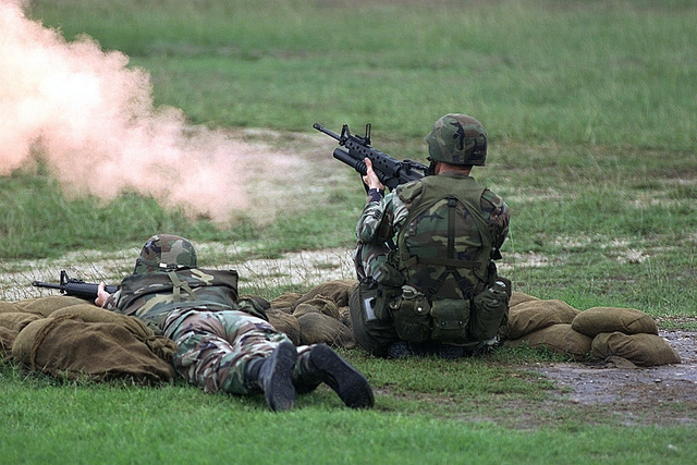Air Force Materiel Command's STAFF Sergeant Timothy A. Kane (Grenadier and kneeling) and US Air Force STAFF Sergeant Jerry W. Zaborksky (Rifleman and lying down) fire at targets down range as an evaluator looks on during the combat weapons competition at DEFENDER CHALLENGE 2000 at Camp Bullis, Texas. Defender Challenge is the annual Air Force wide competition sponsored by Air Force Security Forces. This competition showcases the talents and capabilities of 13 international Security Forces teams in seven physical fitness, base defense and policing skills over six days