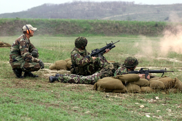 Royal Air Force Regiment's Corporal Antony Doherty (Grenadier and kneeling) and Flight Lieutenant Kristian Cressy (M16 rifleman and lying down) fire at targets down range as an evaluator looks on during the combat weapons competition of DEFENDER CHALLENGE 2000 at Camp Bullis, Texas. Defender Challenge is the annual Air Force wide competition sponsored by Air Force Security Forces. This competition showcases the talents and capabilities of 13 international Security Forces teams in seven physical fitness, base defense and policing skills over six days