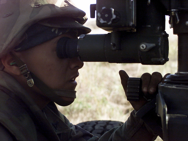 A close up view of US Marine Corps Lance Corporal (LCPL), Enrique J. Cruz, 3rd Battalion, 12th Marine Regiment, 3D Marine Division, as he looks through the M137 Panoramic Telescope while manning the M198 155mm Howitzer, at Gun Position 10, East Camp Fuji, Japan. This training area is part of the unit's nine firing day relocation shoot, designed to enhance military occupational specialty proficiency within the artillery field