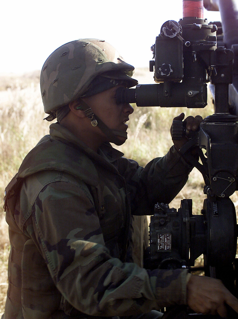 US Marine Corps Lance Corporal (LCPL), Enrique J. Cruz, 3rd Battalion, 12th Marine Regiment, 3D Marine Division, looks through the M137 Panoramic Telescope while manning the M198 155mm Howitzer, at Gun Position 10, East Camp Fuji, Japan. This training area is part of the unit's nine firing day relocation shoot, designed to enhance military occupational specialty proficiency within the artillery field
