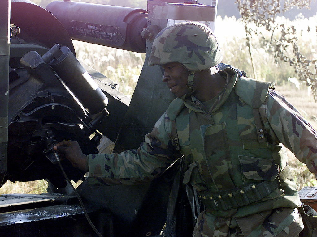US Marine Corps Lance Corporal (LCPL), Shamari R. Bethancourt, 3rd Battalion, 12th Marine Regiment, 3D Marine Division, attaches the lanyard before plugging the M198 155mm Medium Towed Howitzer at Gun Position 10, East Camp Fuji, Japan. This training area is part of the unit's nine firing day relocation shoot, designed to enhance military occupational specialty proficiency within the artillery field