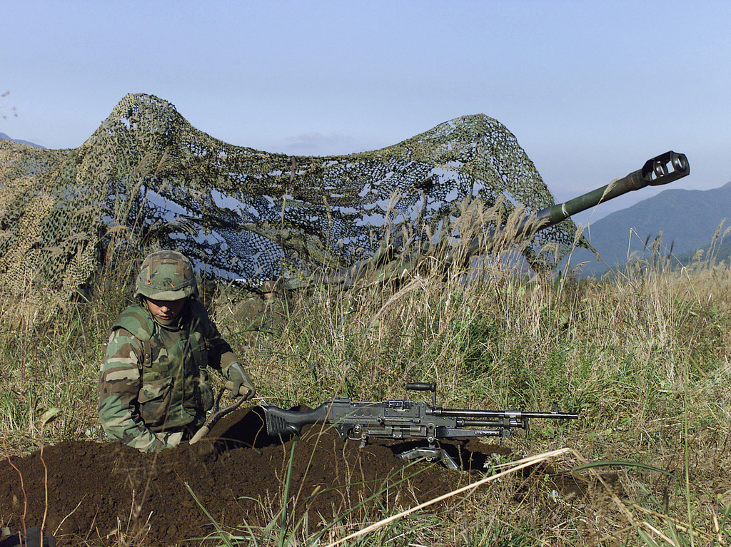 US Marine Lance Corporal (LCPL), Joseph T. Flamand, 3rd Battalion, 12th Marine Regiment, 3D Marine Division, digs a fox hole for his tripod mounted M-240G Automatic Machine Gun. He provides a defensive position for the M-198 155mm Howitzer at Gun Position 10, East Camp Fuji, Japan. This training area is part of the units nine firing day relocation shoot, designed to enhance military occupational specialty proficiency within the artillery field