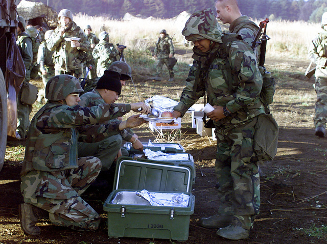 US Marines from 3rd Battalion, 12th Marine Regiment, 3D Marine Division, are served morning chow in the field, at Gun Position 10, East Camp Fuji, Japan. This training area is part of the unit's nine firing day relocation shoot, designed to enhance military occupational specialty proficiency within the artillery field
