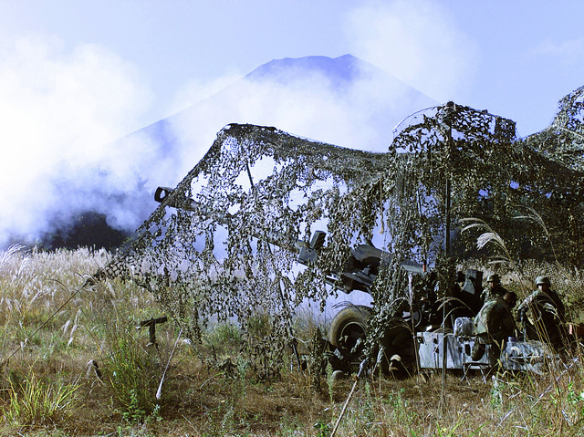 US Marines from 3rd Battalion, 12th Marine Regiment, 3rd Marine Division, fire the M198 155mm Medium Towed Howitzer. Marines at Gun Position 10, East Camp Fuji, Japan, are part of the unit's nine firing day relocation shoot, designed to enhance military occupational specialty proficiency within the artillery field