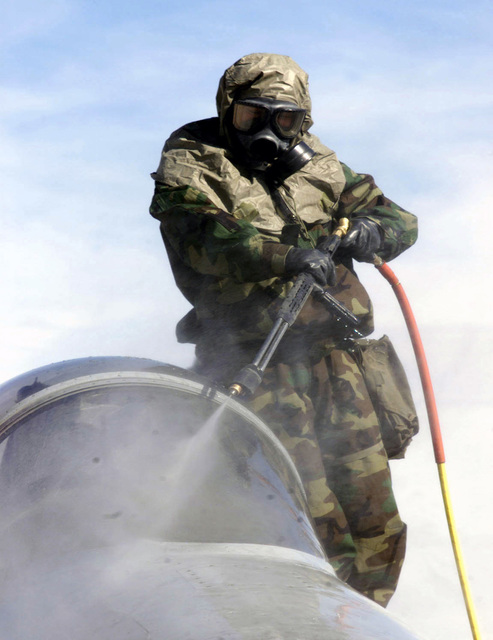 Lance Corporal (LCPL) Arias, of Maine Wing Support Squadron 373 washes the nose of a F/A 18C Hornet during a decontamination exercise during COMBINED ARMS EXERCISE (CAX) 2-01. LCPL Arias is in Mission-Oriented Protective Posture Response level 4 (MOPP-4) gear, wearing the battledress overgarment (BDO), chemical protective footwear cover (CPFC), glove set, and the M40 Chemical-Biological Field Mask with protective hood. CAX is a two week course designed for practical experience in tactics, desert operations, and combined arms exercises