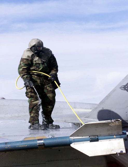 Lance Corporal (LCPL) Arias, of Marine Wing Support Squadron 373, washes the wing of a F/A 18C Hornet in a decontamination exercise during COMBINED ARMS EXERCISE (CAX) 2-01. LCPL Arias is in Mission-Oriented Protective Posture response level 4 (MOPP-4) gear, wearing the battledress overgarment (BDO), chemical protective footwear cover (CPFC), glove set, and the M40 Chemical-Biological Field Mask with protective hood. CAX is a two week course designed for practical experience in tactics, desert operations, and combined arms exercises