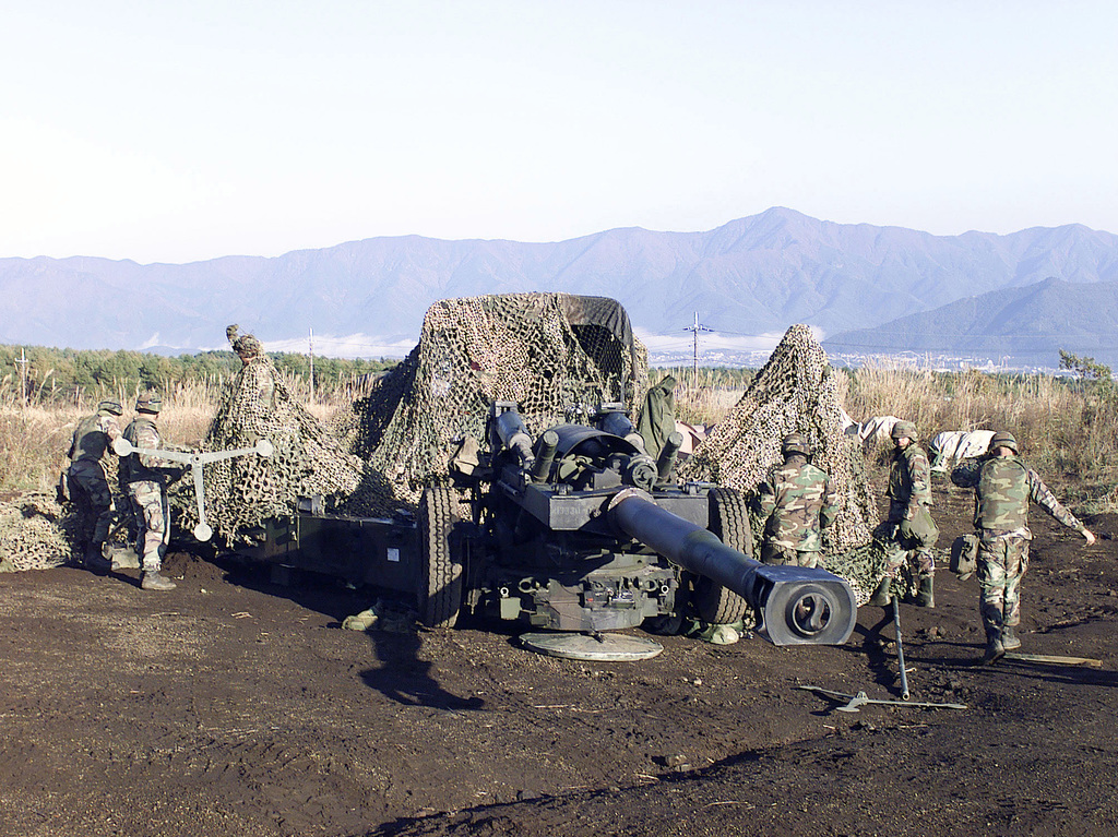 US Marines from 3rd Battalion, 12th Marine Regiment, 3D Marine Division, set up camouflage netting over their M198 155mm Medium Towed Howitzer at Gun Position 99, East Camp Fuji, Japan. The training area is part of the unit's nine firing day relocation shoot, designed to enhance military occupational specialty proficiency within the artillery field