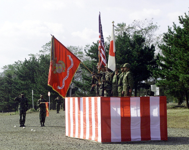 Lieutenant Colonel William Jones (left) and Sergeant Kenneth Lucas (guidon) proudly observe both the Marine and Japanese Color Guard standing tall, as they render proper respect for both National Anthems at the Opening Ceremony of Forest Light 2000. Forest Light is a cultural enhancing, combined arms exercise in which Marines from 1ST Battalion, 6th Marine Regiment train with soldiers from the 44th Infantry Regiment, Japanese Ground Self Defense Force (JGSDF). The units train side by side teaching each other various weapons systems, different tactical offenses and defenses, as well as close combat skills