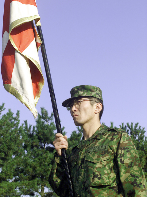 Lieutenant Hasegawa, a Japanese Ground Self Defense Force (JGSDF) soldier, proudly holds the 44th Infantry Regiment guidon at the Opening Ceremony during Forest Light 2000. Forest Light is a cultural enhancing, combined arms exercise in which Marines from 1ST Battalion, 6th Marine Regiment train with soldiers from the 44th Infantry Regiment, JGSDF. The units train side by side teaching each other various weapons systems, different tactical offenses and defenses, as well as close combat skills