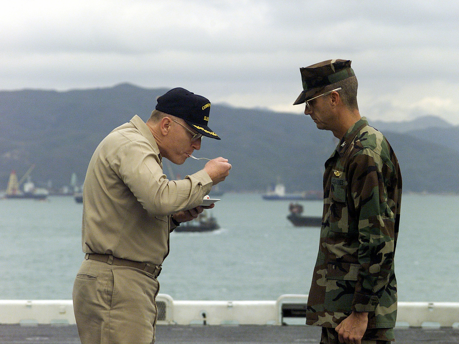 US Navy Captain (CAPT) F. Lee Touchberry, watches carefully as US Marine Corps Colonel (COL), James Lowe, Commanding Officer of the 31st Marine Expeditionary Unit (MEU), takes a bite from the Marine Corps 225th birthday cake. The officers are on the flight deck of the USS Essex (LHD 2), while in Hong Kong, China. US Marine and Naval Forces Unit spent two months participating in various training operations on and off the coast of Okinawa, Japan, Sasebo, Japan, Pohang, Korea, and Hong Kong, China
