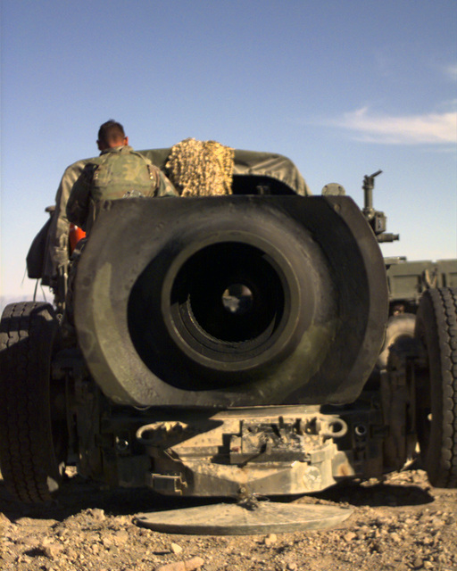 View of the business end of an M198 Medium Towed Howitzer. US Marines from Third Battalion, Eleventh Marine Regiment, First Marine Division use combinations of variable timed fuses and different powered charges, including super 8, green, white, and red bag, also an assortment of 155mm rounds including high explosive, concrete piercing, white phosphorous, illumination, killer junior, beehive, anti-tank and anti-personnel rounds to create specific effects on target. The entire weapons system, which weighs 16,000 pounds, is manned by 7 men and a chief and can fire up to 30,000 meters. The most common round used during training was the High Explosive (HE) round which weighs 96 pounds and has ...