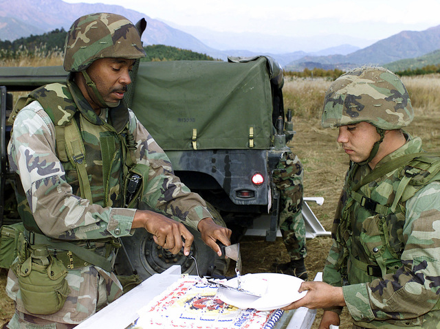 US Marines Corps STAFF Sergeant (SSGT) Summer O. Fields, 3rd Battalion, 12th Marine Regiment, 3D Marine Division, serves cake to his Marines during the Marine Corps 225th Birthday Cake Cutting Ceremony at Gun Position 99, East Camp Fuji, Japan. This training area is part of the unit's nine firing day relocation shoot, designed to enhance military occupational specialty proficiency within the artillery field