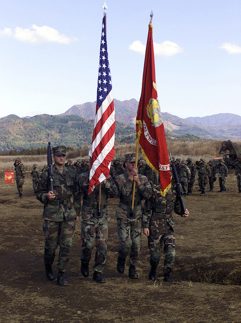 US Marines from 3rd Battalion, 12th Marine Regiment, 3D Marine Division, retire the colors from the Marine Corps Birthday Cake Cutting Ceremony at Gun Position 99, East Camp Fuji, Japan. This training area is part of the unit's nine firing day relocation shoot, designed to enhance military occupational specialty proficiency within the artillery field