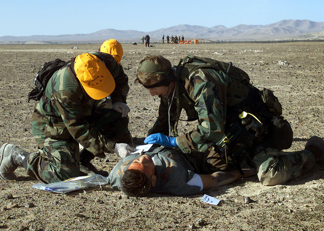 """A US Air Force Pararescueman (Right) from the the 129th Air Rescue Wing, Moffett Field, Mountain View, California, and two Commandos of the Chilean Air Force treat a """"survivor"""" in a mock disaster response in the Atacama Desert of northern Chile. The disaster scenario was part of a joint-nation exercise, CHILE TCA 2000, between the California Air National Gaurd, Wilford Hall Medical Center, Lackland Air Force Base, Texas, and the Fuerza Aerea de Chile"""