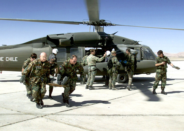 Following initial treatment by US Air Force Pararescuemen of the 129th Air Rescue Wing, Moffett Federal Airfield, Mountain View, California, and Commandos of the Fuerza Aerea de Chile, victims are loaded onto a Chilean UH-60 Blackhawk helicopter for trasnport to field medical facilities set up in the Atacama Desert. The mass casualty evacuation, Exercise CHILE TCA 2000, was a joint-nation effort of the California Air National Guard and the Chilean Air Force
