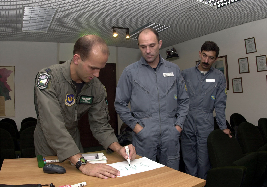 "US Air Force Captain Kevin ""FLASH"" Gordon, fighter pilot with the 555th Fighter Squadron, Aviano Air Base, Italy, provides an example of how a low frequency radar signal works to Captain Tihomir Rezashki and Major Veselin Milushev both of the Bulgarian Air Force"