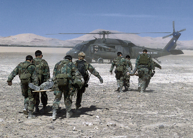 US Air Force Pararescuemen of the 129th Air Rescue Wing, Moffett Field, Mountain View, California, and Chilean Commandos of the Fuerza Aerea de Chile carry victims of a simulated crash to a Chilean UH-60 Blackhawk helicopter for transport to a medical facility in the Atacama Desert set up by personnel of the California Air National Guard and Wilford Hall Medical Center, Lackland Air Force Base, Texas, during Exercise CHILE TCA 2000. The event, part of an exchange dating back to 1995, was designed to test interoperability of U.S. and Chilean forces in disaster response