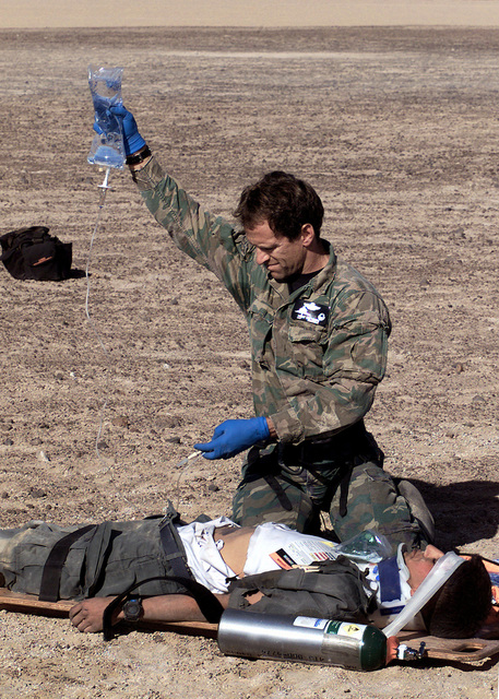 US Air Force SENIOR MASTER Sergeant Tim Young of the 129th Air Rescue Wing, Moffett Field, Mountain View, California, treats an injured victim at a simulated crash site in the Atacama Desert during CHILE TCA 2000, a mass casualty evacuation exercise involving the California Air National Guard and ERSAM, the air evac unit of the Fuerza Aerea de Chile