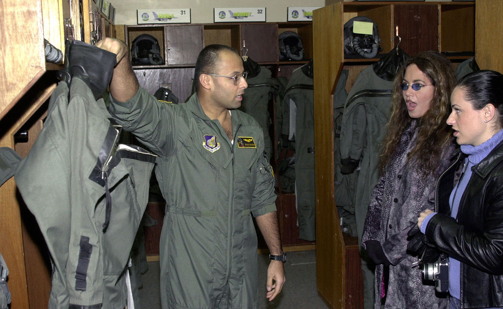US Air Force Captain Sam Mann of the 14th Fighter Squadron, Misawa Air Base, Japan, explains to country music recording artist, Lisa Angelle (left) and, Mary Therese, Ms. Georgia, how cold weather gear increases the chance of survival of a downed pilot. The women were given a tour of the fighter squadron during Operation SEASONS GREETINGS 2000 sponsored by the United Service Organization (USO)