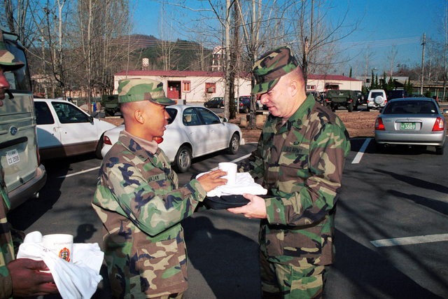 Private First Class Amazan, left, presents Sergeant Major of the Army Jack L. Tilley with an organizational T-shirt and coffee cup in commemoration of his visit with Charlie Company, 1ST Battalion, 52nd Aviation Regiment, and 17th Aviation Brigade