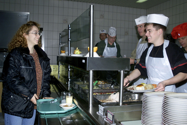 US Air Force AIRMAN First Class Dellana Perez is served a Thanksgiving meal at the Mosel Dining Hall, Spangdahlem Air Base, Germany. Spangdalem s Group and Squadron Commanders along with the First Sergeant showed their gratitude for the work and dedication of the Wings Airmen, by serving the holiday dinner. Listed (front to back) Daniel Hoffman, US Air Force Brigadier General Donald Hoffman, 52nd Fighter Wing Commander, Colonel (COL) Gregg Sanders, 52nd Support Group Commander, and COL Joe B. Drane III, 52nd Medical Group Commander, of Spangdahlem Air Base, Germany