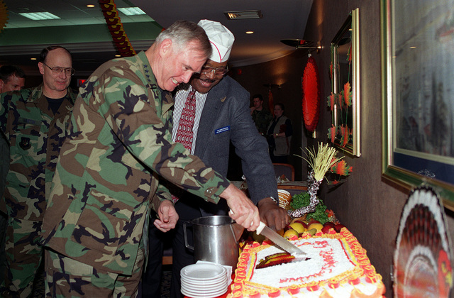 US Air Force General (GEN) Michael Ryan, Air Force CHIEF of STAFF and Mr. Lincoln Breckenridge, Food Service Supervisor, Incirlik Air Base Turkey, participate in the cutting of the Thanksgiving Day cake, as GEN Gregory Martin, Commander, US Air Forces in Europe, watches the event