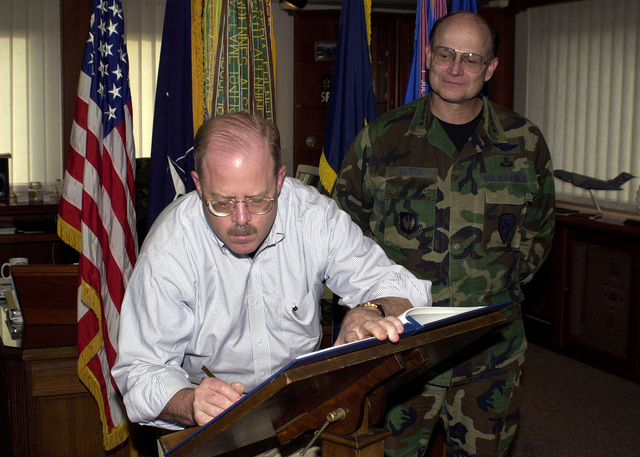 US Air Force General Gregory S. Martin, Commander, United States Air Force Europe, watches as the Honorable F. Whitten Peters, Secretary of the Air Force (SECAF), signs the United States Air Force Europe guest book upon SECAF Peters arrival to Ramstein Air Base, Germany