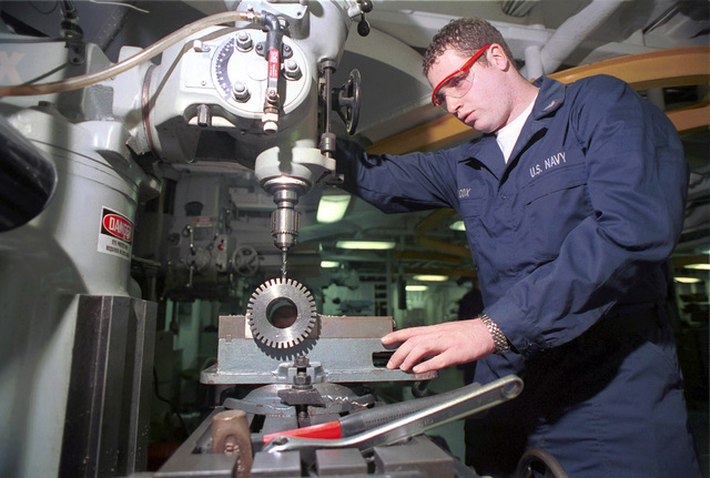 Machinery Repairman Third Class Aaron J. Wilcox uses a drill press to modify a part for the ship's incinerator in the Metal Shop on board USS Harry S. Truman (CVN 75). TRUMAN is on a scheduled six-month deployment to the Mediterranean Sea and Arabian Gulf