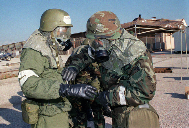 Dressed in chemical warfare gear during the quarterly 39th Wing Readiness Day at Incirlik Air Base, Turkey, US Air Force STAFF Sergeant Michael Dealy and US Air Force AIRMAN Gerald Allen check each other over with a rapid deacon M-291 Kit