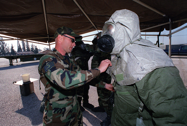 During the quarterly 39th Wing Readiness Day at Incirlik Air Base, Turkey, US Air Force STAFF Sergeant David Hughes assists US Air Force AIRMAN Gerald Allen in loosening his chemical gear hood in the first station of the Chemical Contamination Area