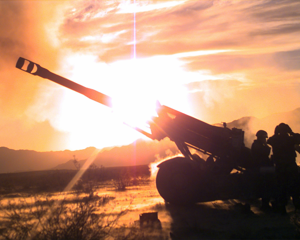 """US Marine Corps (USMC) personnel from Gun Two, Battery """"T"""", 5th Battalion, 11th Marine Regiment fire an M198 155mm Towed Howitzer as the sun sets on USMC Air Ground Combat Center (MCAG) Twenty-nine Palms, California (CA)"""