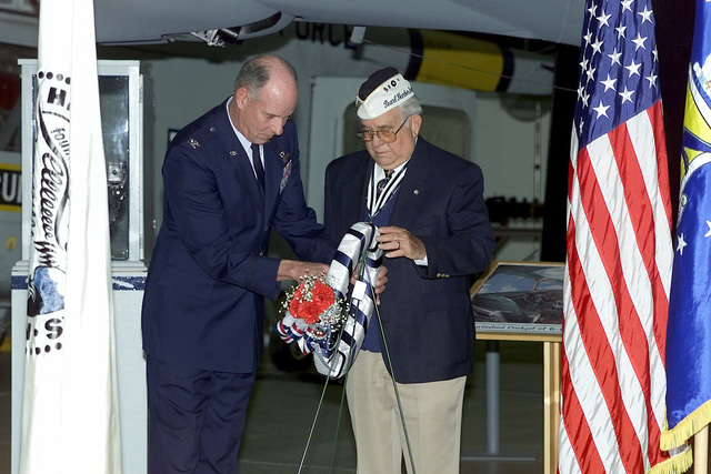 A Delaware area survivor of Pearl Harbor and US Air Force Colonel Mills of the 436th Air Wing, Dover Air Force Base, Delaware, present a wreath during the Pearl Harbor Day Remembrance Ceremony held at the Air Mobility Command (AMC) Museum, Dover AFB