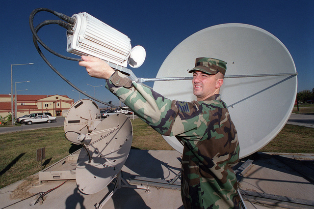 US Air Force STAFF Sergeant Greg Strong of the weather flight, adjusts a weather satillite dish to get optumum signal reception, at Incirlik Air Base, Turkey