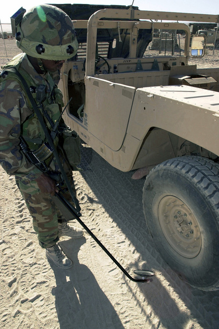 A soldier, wearing Multiple Integrated Laser Engagement System (MILES) gear, from 3rd Brigade, 101st Airborne Division uses a mirror to visually inspect the underside of an M998 High-Mobility Multipurpose Wheeled Vehicle (HMMWV) during training at Fort Irwin's National Training Center. The MILES gear is worn on helmet and upper body, to simulate combat conditions where one can be shot electronically without injury or fatality, yet instills a sense of the real danger of combat