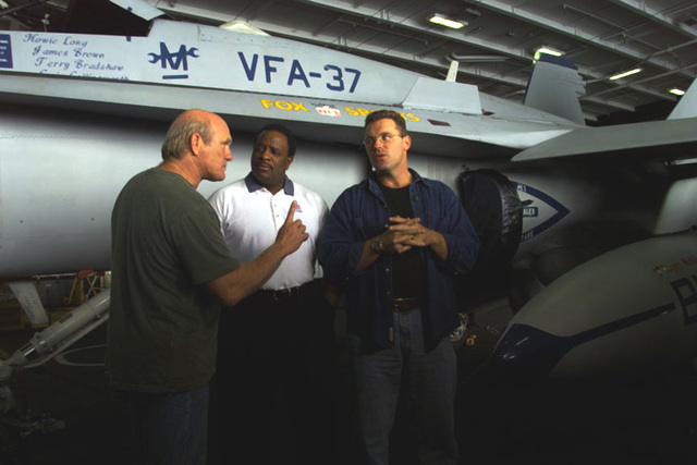 """Fox Sports celebrities Howie Long, James Brown, and Terry Bradshaw discuss the taping of their Pre-Game Show in front of an F/A-18 Hornet from Fighter Attack Squadron Thirty Seven (VFA-37) the """"BULLS"""", upon their arrival on board USS Harry S. Truman (CVN 75). The Fox Sports hosts are on board to tape their popular NFL Pre-Game Show aired on the FOX Network. TRUMAN is on a scheduled six-month deployment to the Mediterranean Sea and Arabian Gulf"""