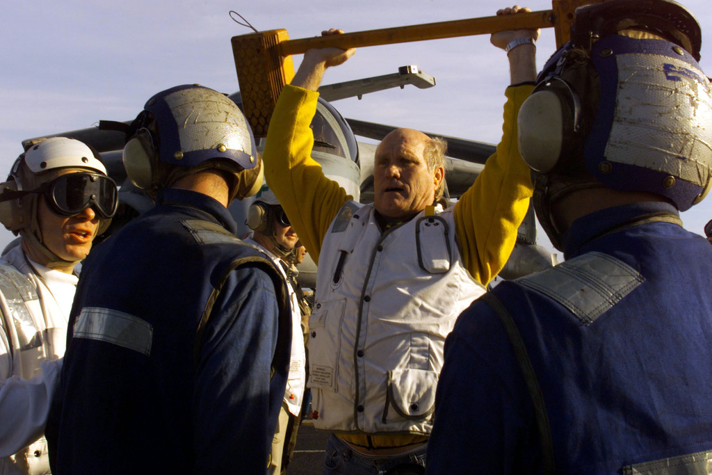 FOX Sports celebrity Terry Bradshaw demonstrates an alternate use for wheel chocks to members of the flight deck crew during his visit on board the USS Harry S. Truman (CVN 75). The Fox Sports host is aboard TRUMAN to tape the popular NFL Pre-Game Show aired on the FOX Network, December 2000. TRUMAN is on a scheduled six-month deployment to the Mediterranean Sea and Arabian Gulf