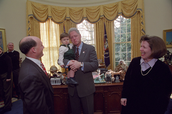 Photograph of President William Jefferson Clinton Holding a Little Boy Present During the Taping of a Weekly Radio Address in the Oval Office at the White House