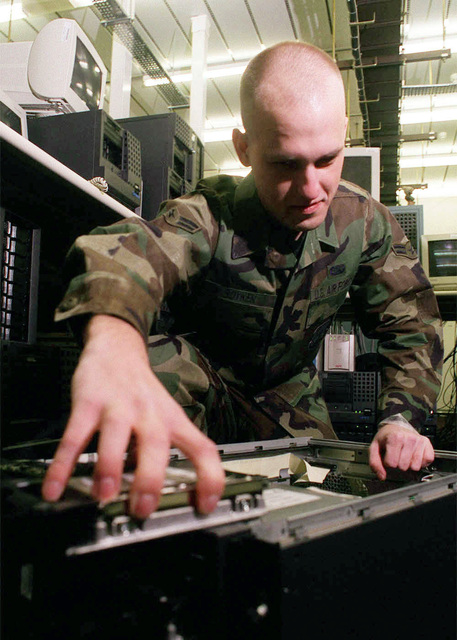 US Air Force AIRMAN First Class Lucas Boyken, a network administrator from the 48th Communications Squadron (CS), 48th Fighter Wing, Royal Air Force Lakenheath, United Kingdom, takes a close up look inside a Dell server. A1C Boyken is a Dell certified technician who has access to all 33 Dell servers at the 48th CS server farm