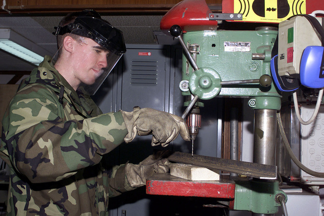 US Air Force AIRMAN Justin Adney, 52nd Civil Engineering Squadron, drills a hole using a drill press machine to build a stand for a gas burner at Spangdahlem Air Base, Germany