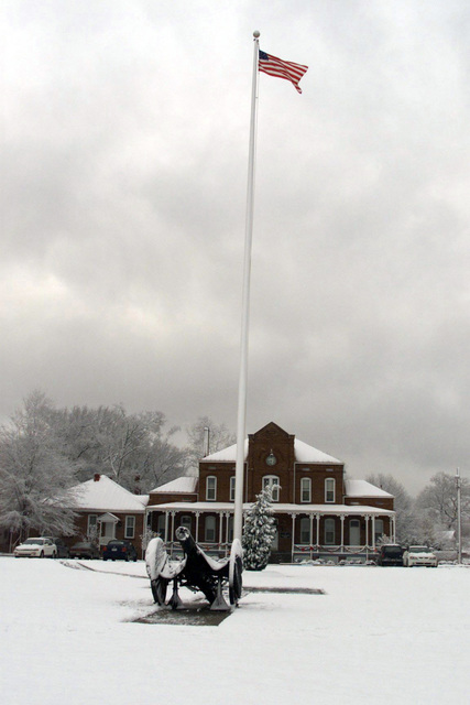 View of the flagpole and cannon on Hedekin Field, Fort McPherson, GA, after a surprise snowfall a week before Christmas. The field is named for Captain Drew Hedekin, the Higher Head Quarters (HHQ) Commander from 1936-1938, an avid Polo player. Behind the flagpole is Van Horn Hall, named for Brigadier General Roberto Van Horn, who held the post's longest command