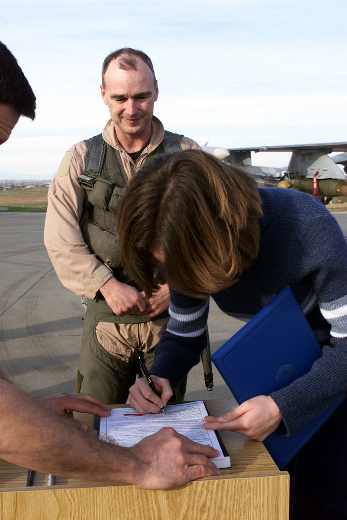 Naomi Hall signs her enlistment papers while US Air Force Brigadier General Bob DuLaney, Co-Commander of the Combined Task Force, Operation NORTHERN WATCH, looks on after a routine flying mission at Incirlik Air Base, Turkey