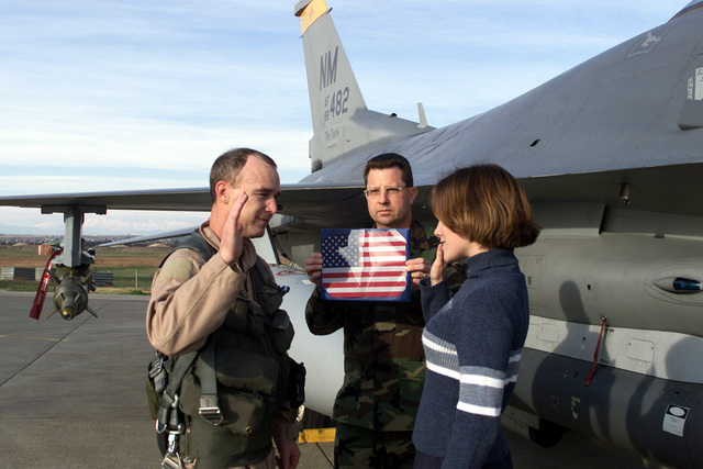 US Air Force Brigadier General Bob DuLaney, Co-Commander of the Combined Task Force, Operation NORTHERN WATCH, enlists Naomi Hall in front of an F-16 Fighting Falcon aircraft after a routine flying mission at Incirlik Air Base, Turkey