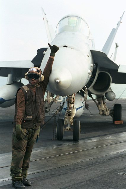 US Navy AIRMAN Bertholet Brisma attached to Fighter Attack Squadron Thirty Seven (VFA-37) gives the ready signal after doing all pre-flight maintenance checks to an F/A-18 Hornet aircraft on the flight deck of USS HARRY S. TRUMAN (CVN 75). Truman is on station in the Persian Gulf in support of Operation SOUTHERN WATCH